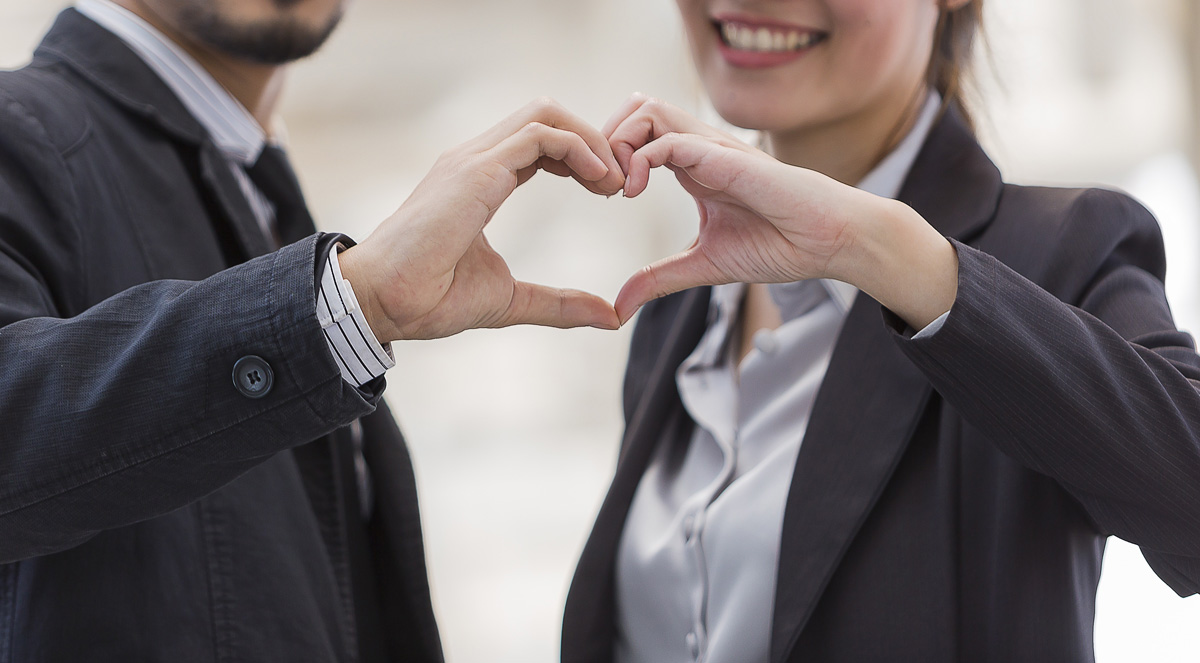 Two business people making a heart by putting both of their hands side by side